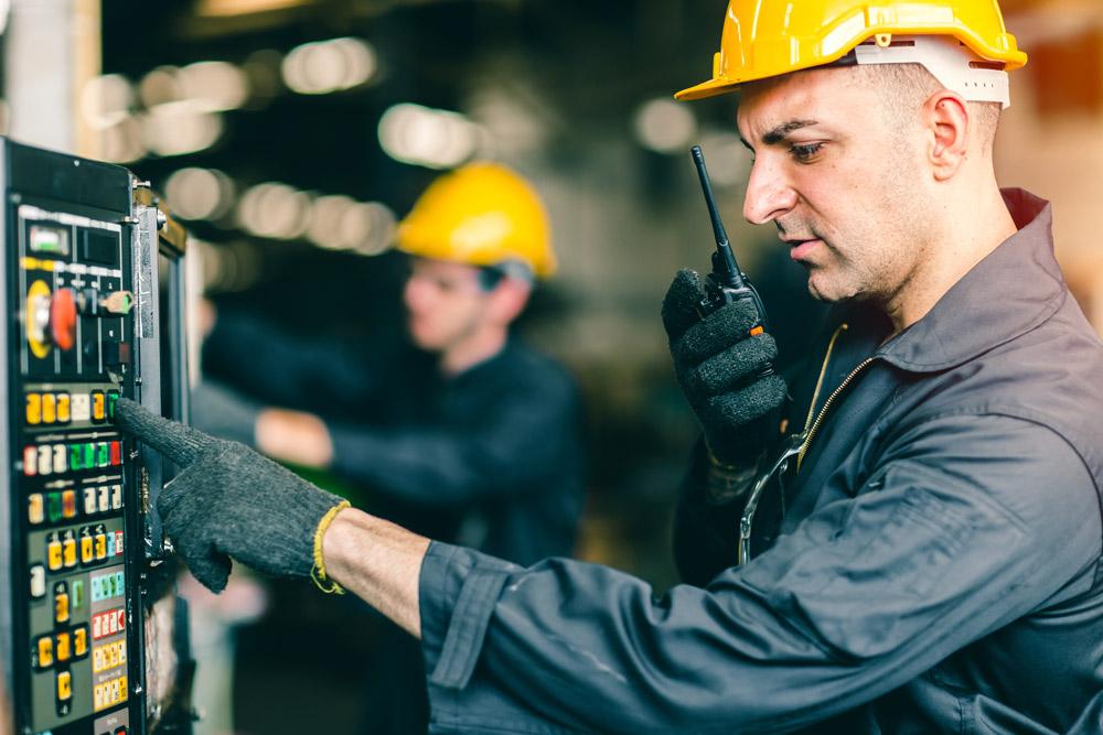Zwei Ingenieure Testen eine elektrische Anlage und Kommunizieren über Funkgerät