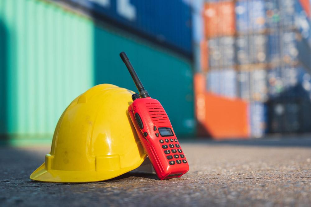 Funkgerät und Helm vor Container