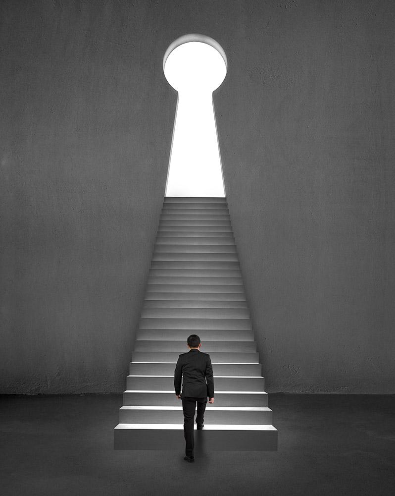 Mann erklimmt Stufen zu Schlüsselloch